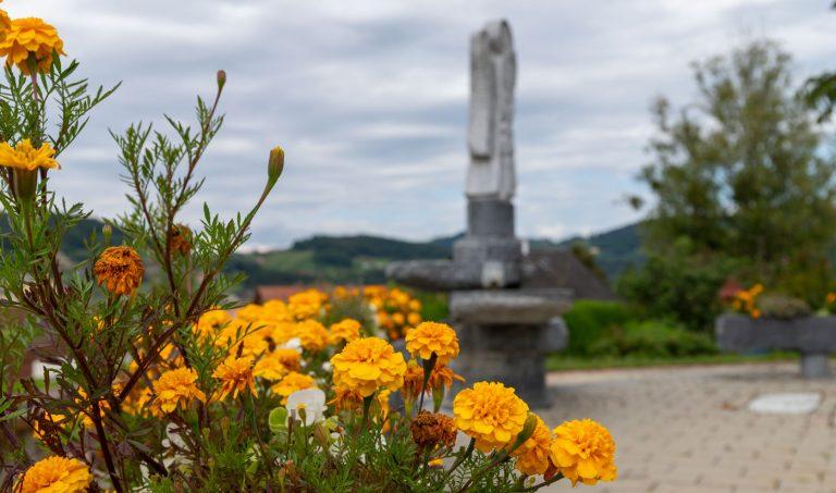 Gedenkstätte mit Blumen im Vordergrund